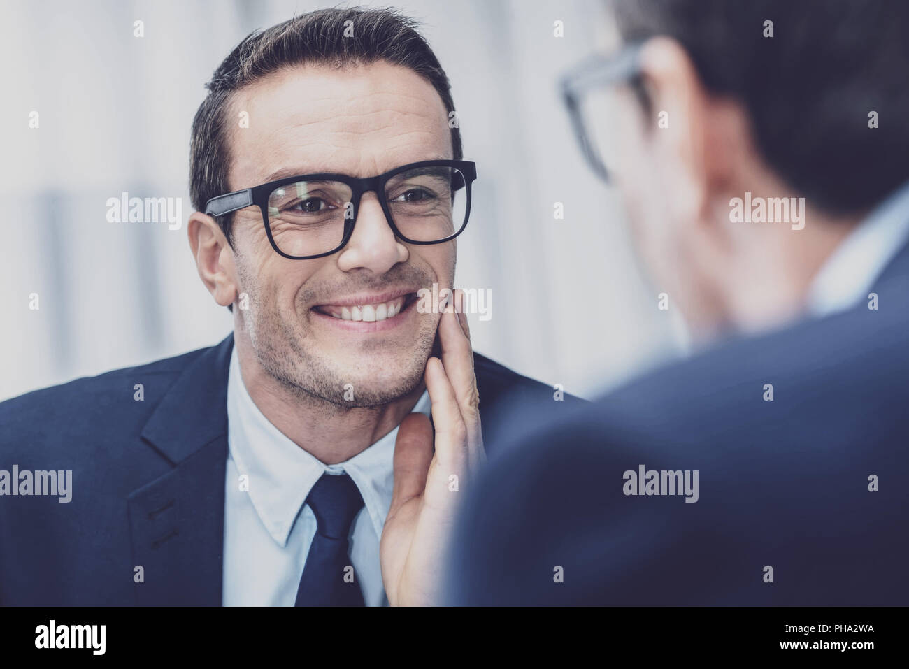 Positive man looking at his face in mirror - Stock Image