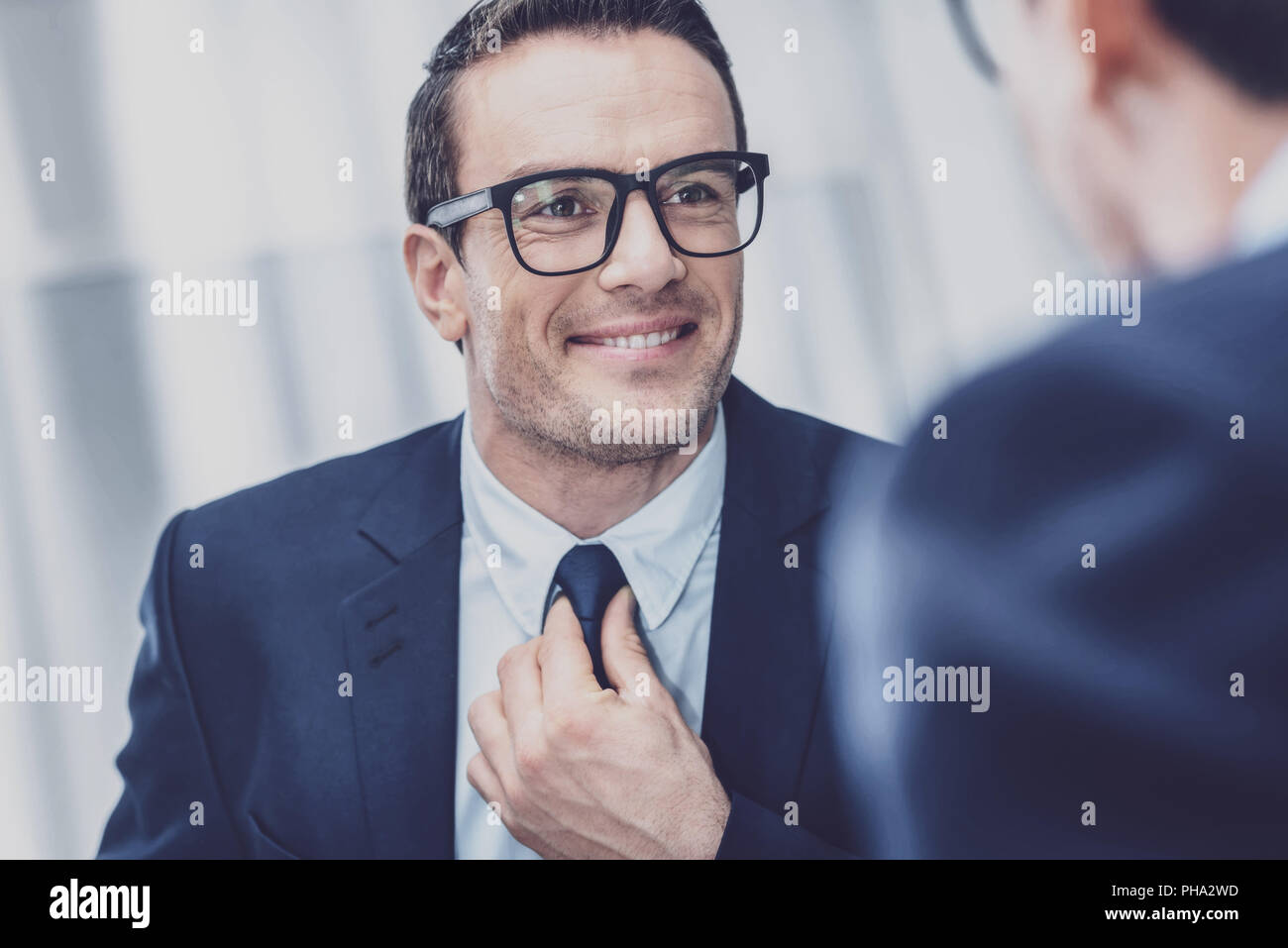Handsome man looking at mirror - Stock Image