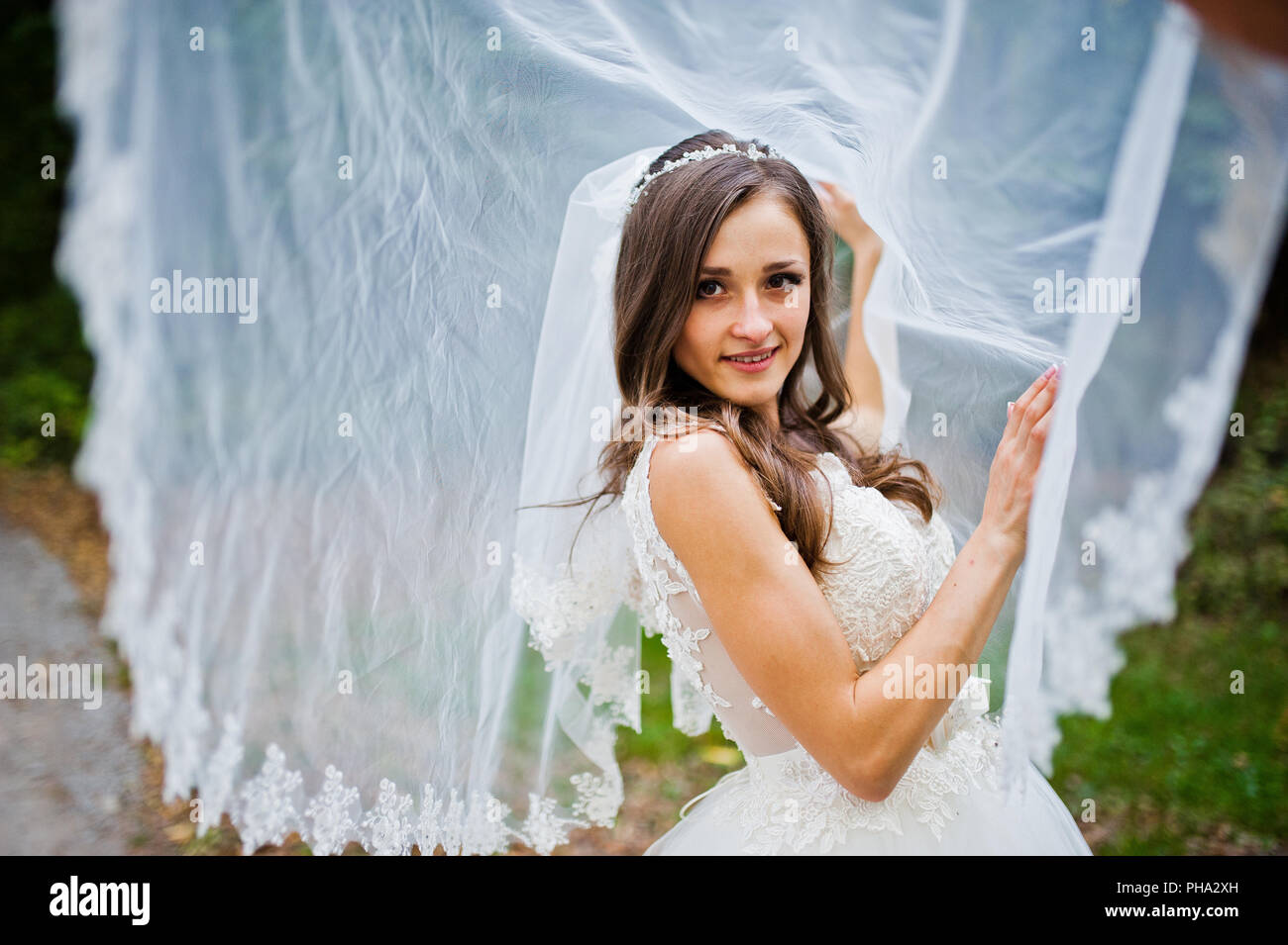 Young coquettish brunette bride play with veil - Stock Image