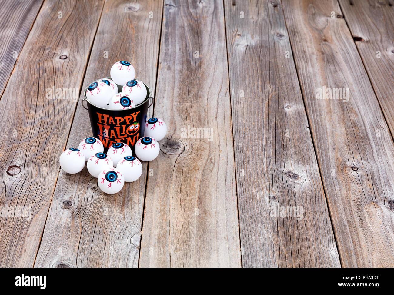 Bucket filled with eyeballs for Halloween season on rustic wood - Stock Image