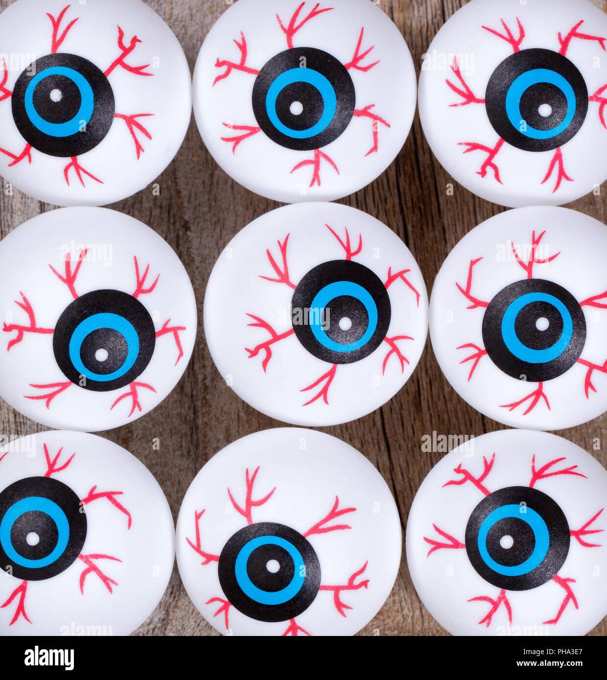 Scary eyeballs for Halloween season on rustic wood - Stock Image