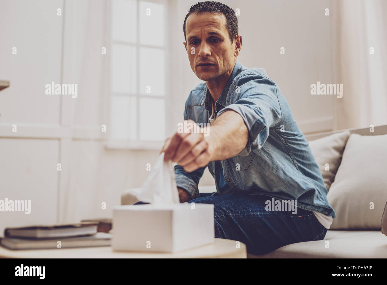 Crying upset man looking forwards - Stock Image