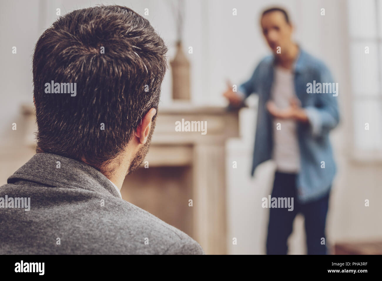 Competent practitioner listening to his visitor - Stock Image