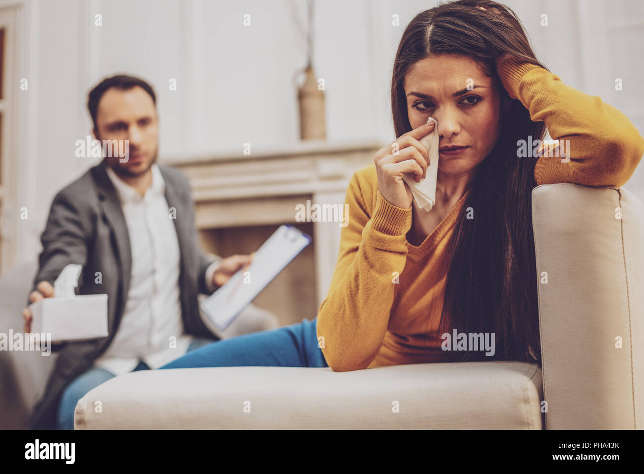 Attentive longhaired female sitting on the couch - Stock Image