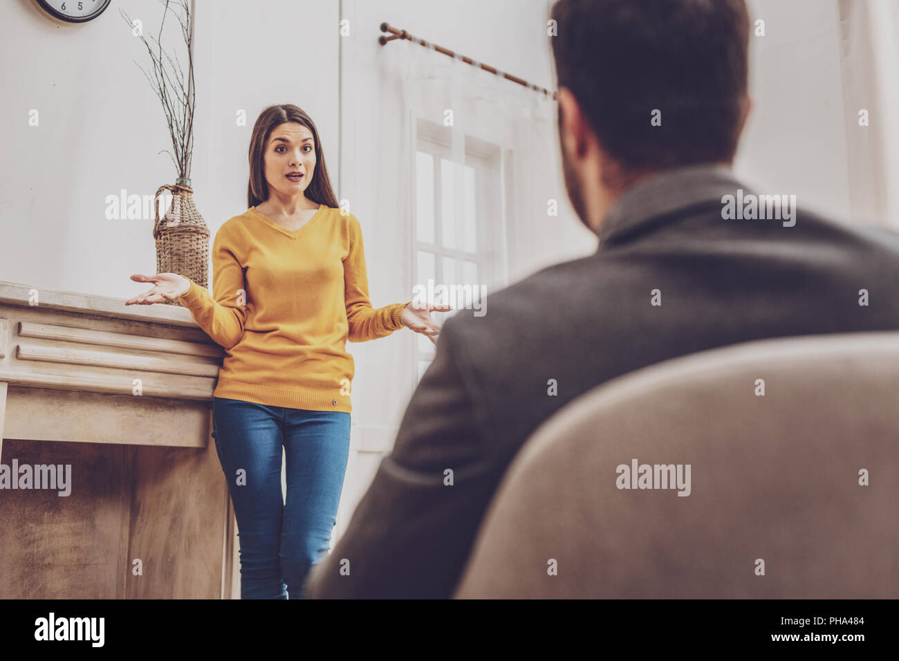 Surprised young woman talking to her man - Stock Image