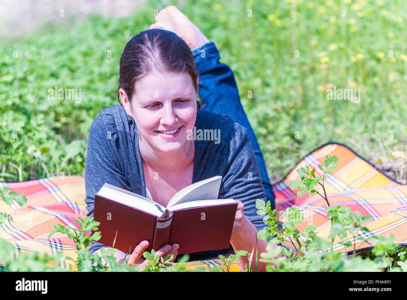 Young woman reading a book - Stock Image
