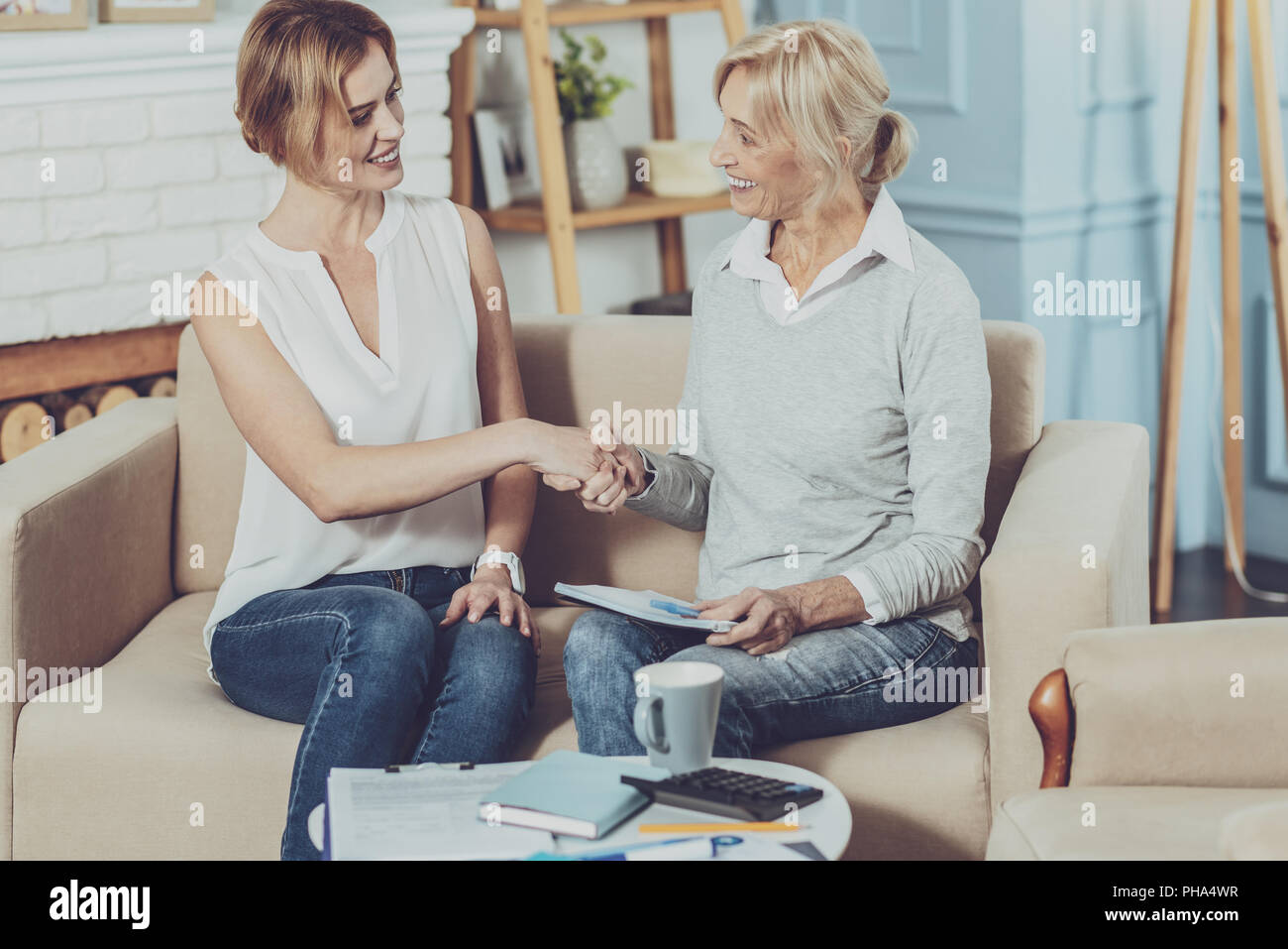 Positive aged woman greeting her financial advisor - Stock Image