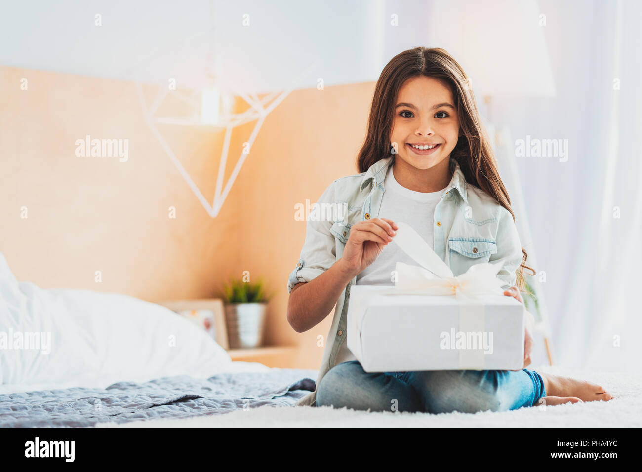 Daughter wondering about her amusing present from parents - Stock Image