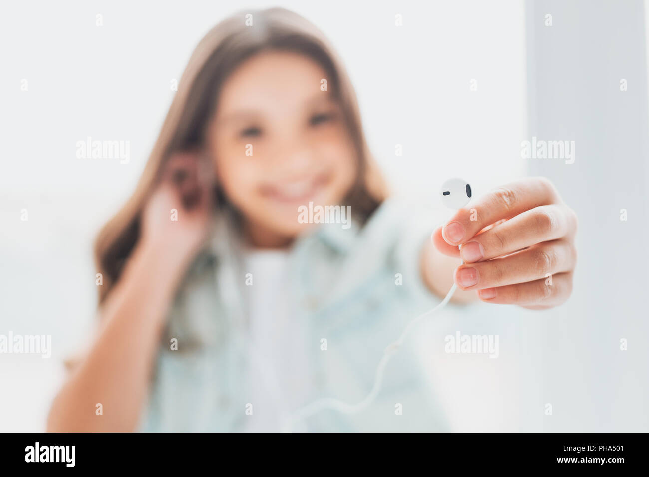 Modern daughter listening to music with earphones - Stock Image