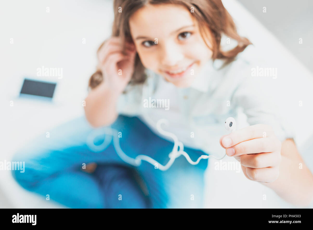 Loving daughter sharing earphones with her caring mother Stock Photo