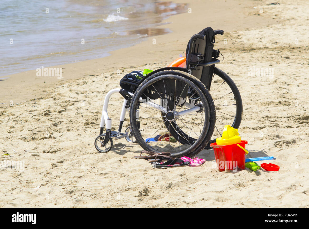 wheel chair on a bech for a disabled child - Stock Image