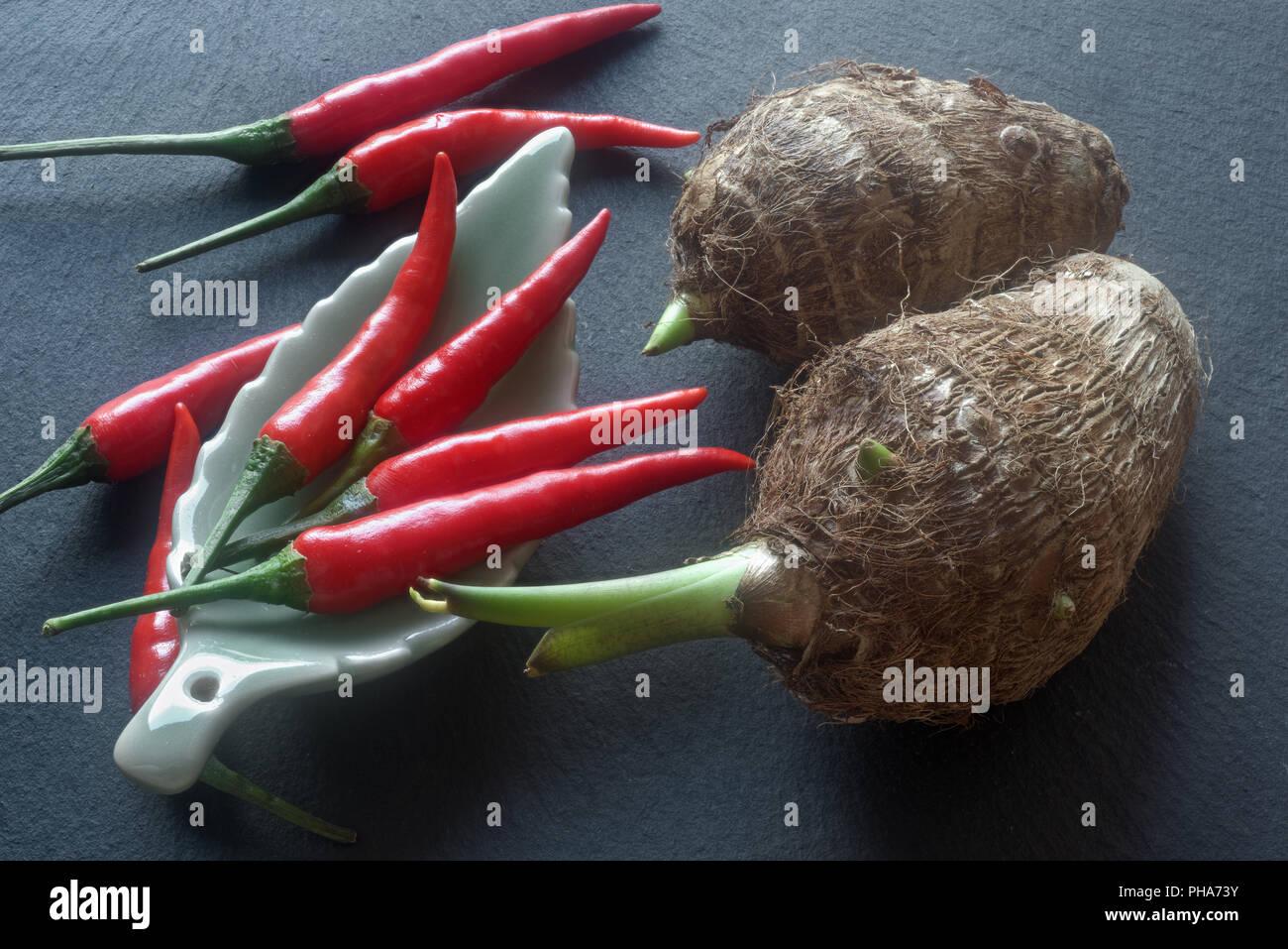 Taro rhizomes and chilis - Stock Image