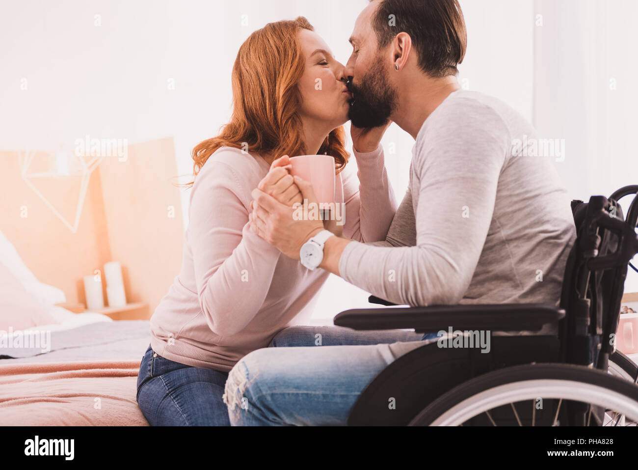 Mid aged loving couple kissing at home - Stock Image
