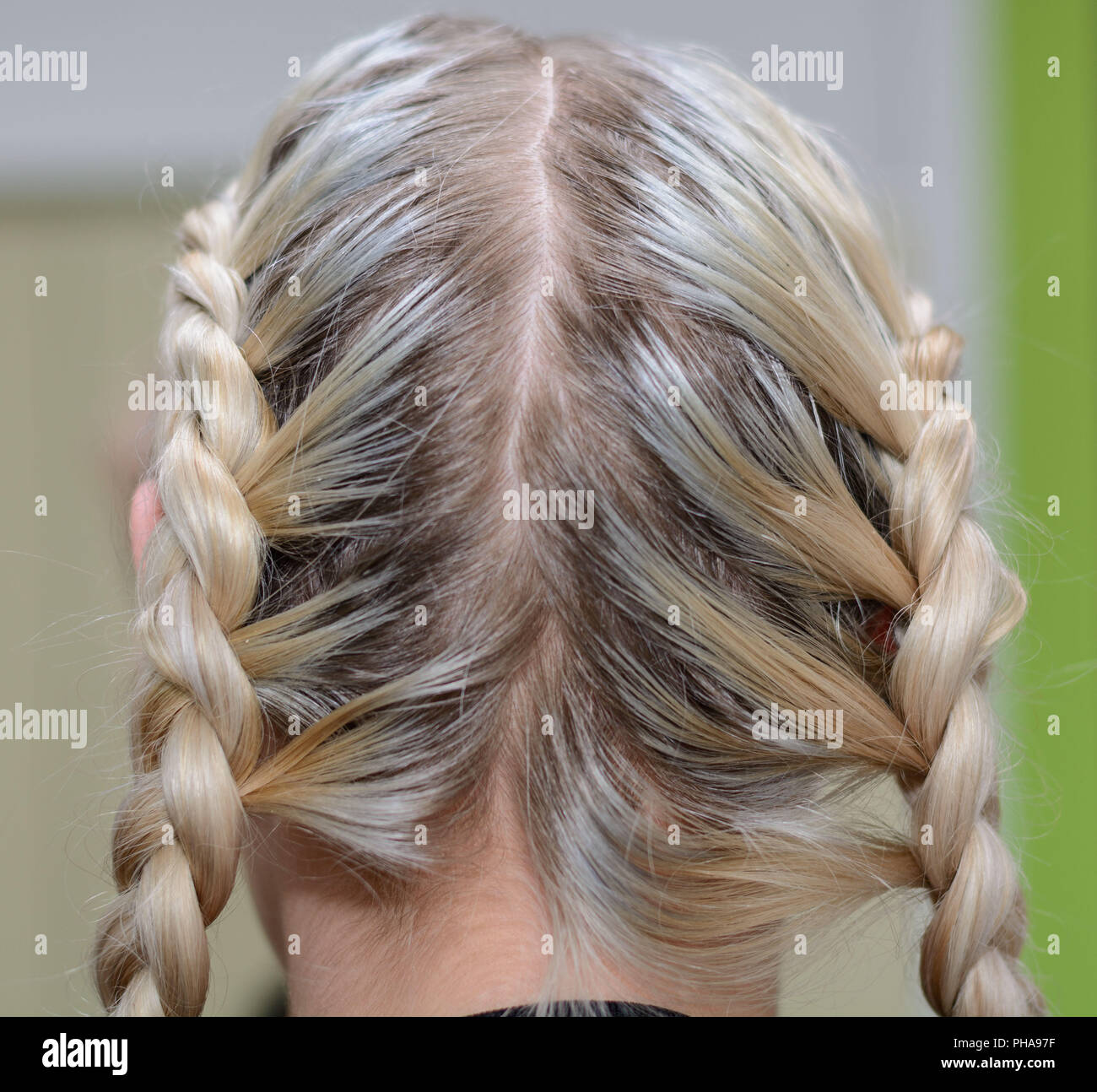 Blonde has braided long hair to two plaits - Stock Image