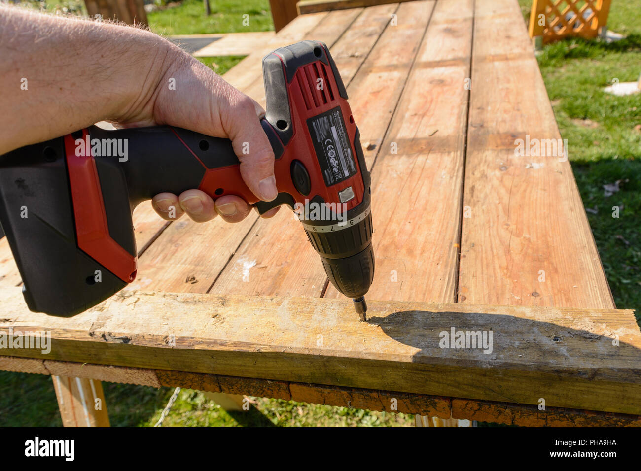 Handyman screwed with cordless screwdriver boards - close-up - Stock Image