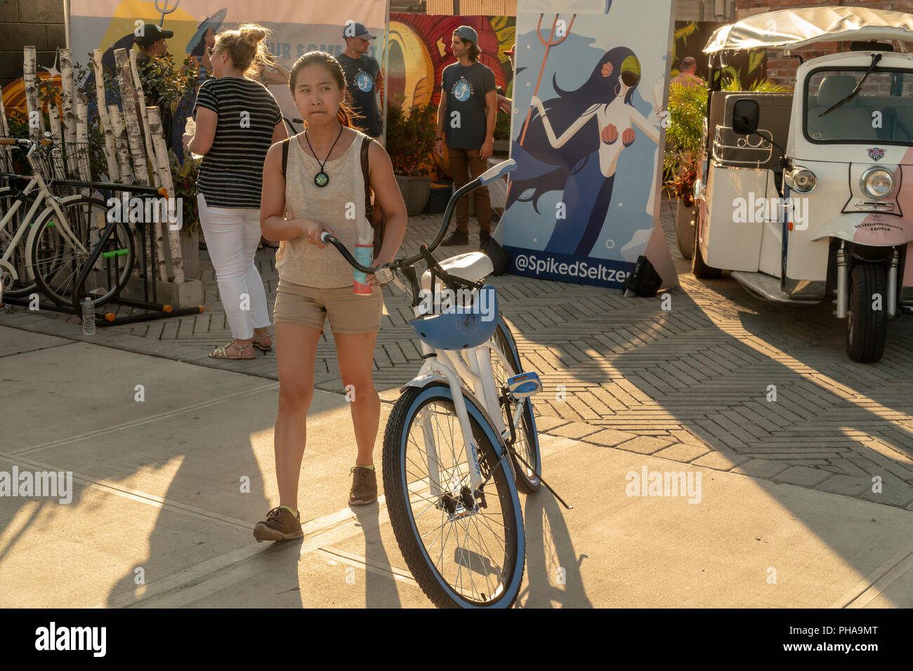 Brooklyn millennials in the Williamsburg neighborhood in Brooklyn receive their free bicycles courtesy of the alcoholic beverage brand, SpikedSeltzer, on Tuesday, August 28, 2018. The Metropolitan Transportation Authority will be shutting down the 'L' train for 15 months, the lifeline in and out of Williamsburg, in April 2019 for Hurricane Sandy related repairs. The giveaway of bicycles is to help ease the transportation pain of the neighborhood's residents, as well as a brand promotion called 'Pour Some Out For The L'  geared toward millennials. SpikedSeltzer is a brand of Anheuser-Busch InBe - Stock Image