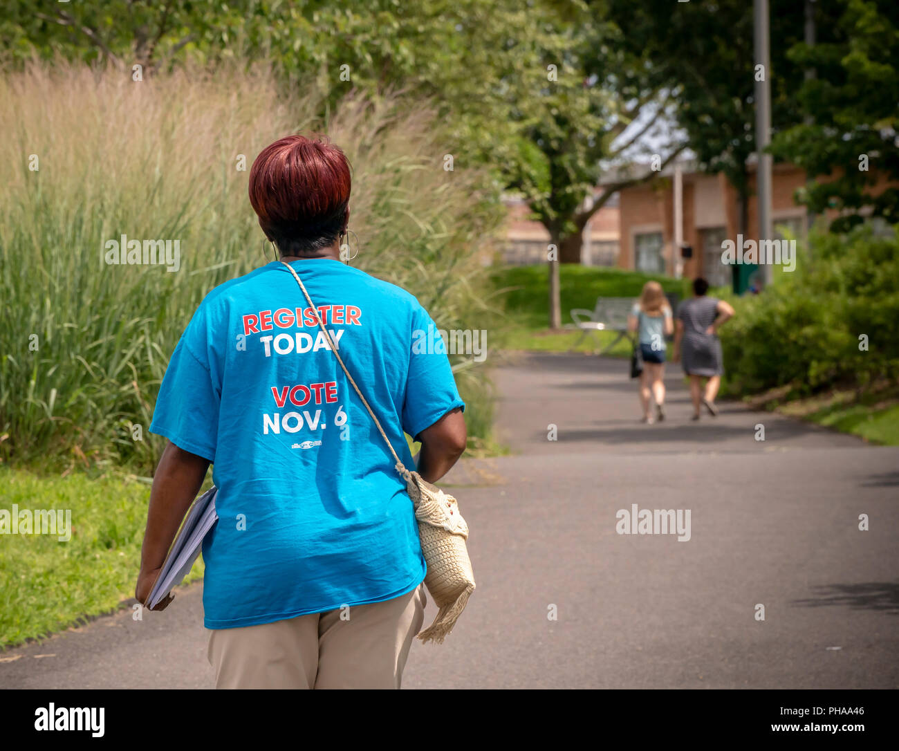 A woman, part of the Voter Registration Outreach Team, walks through Riverfront Park in Newark NJ searching out unregistered potential voters, seen on Saturday, August 25, 2018.  (© Richard B. Levine) - Stock Image