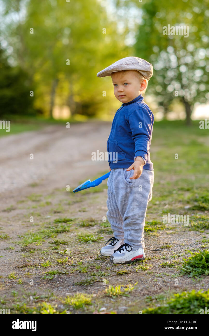Toddler child outdoors. Rural scene with one year old baby boy wearing flat  cap c4535f944bc
