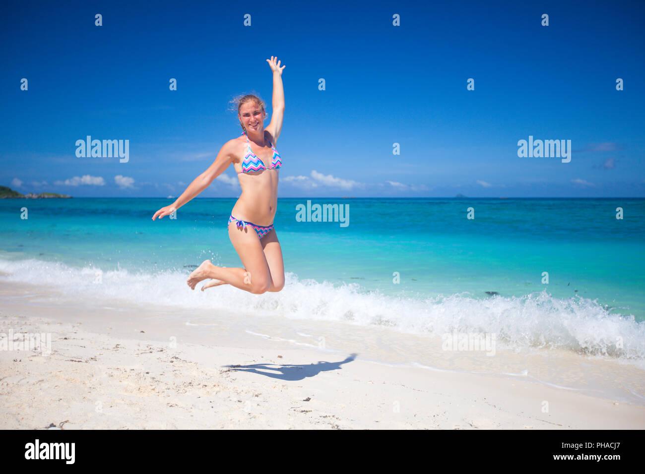 Happy girl in bikini jumping on beach - Stock Image