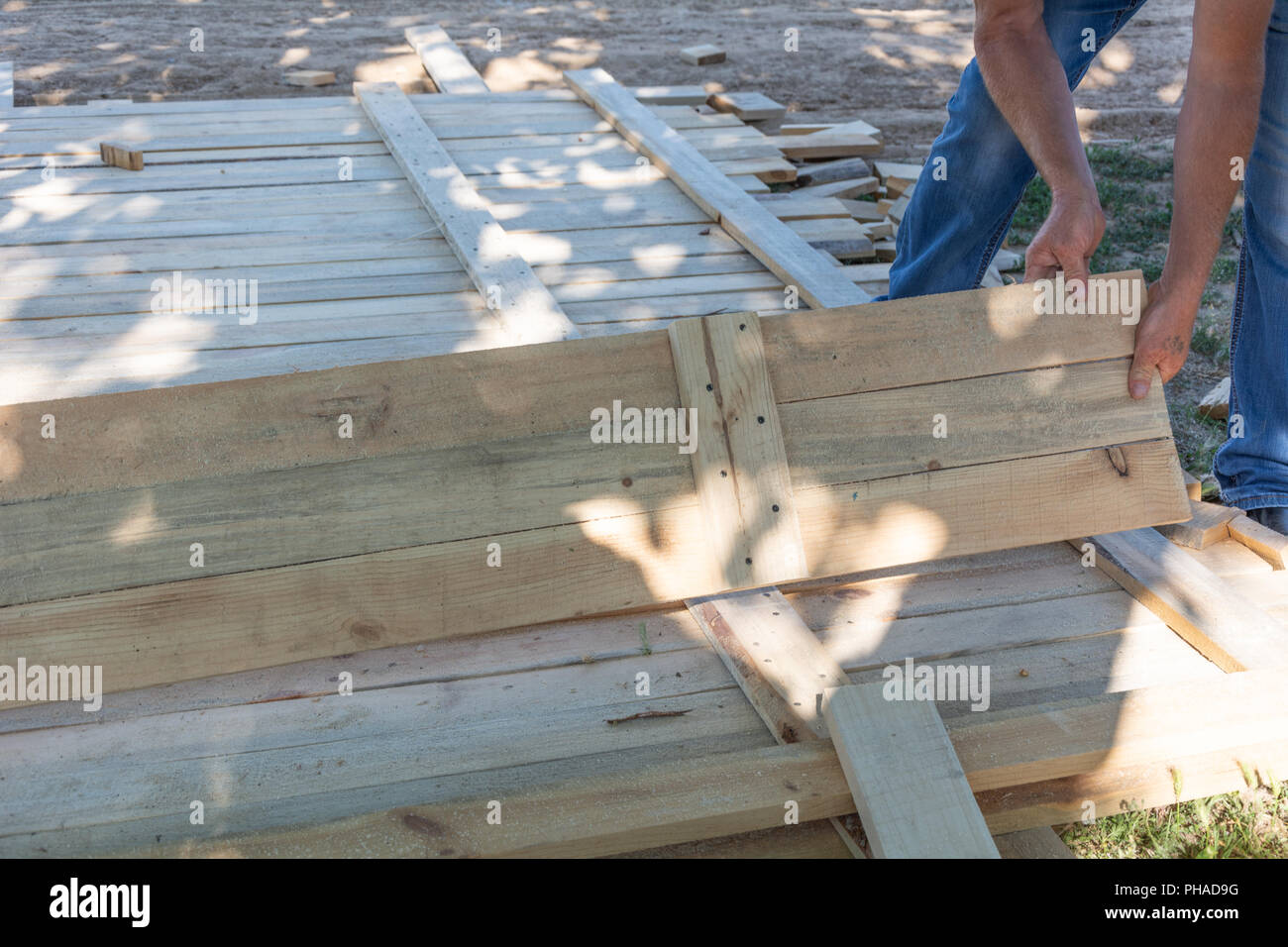 Man building a wooden fence. Workers pick up wooden boards for the fence formwork. Wooden formworks for concrete at construction site. Stock Photo