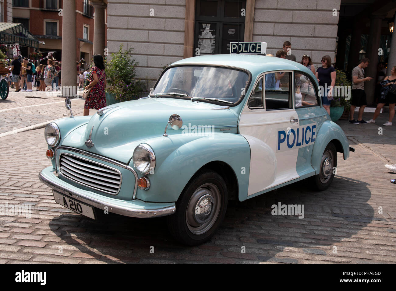 Vintage Morris Minor police car in London, United Kingdom. The Morris Minor is a British car of which more than 1.6million were manufactured between 1948 and 1972. Initially available as a two-door saloon, the range was expanded to include a four-door saloon. It was the first British car to sell over one million units and is considered a classic example of automotive design, as well as typifying Englishness. Stock Photo