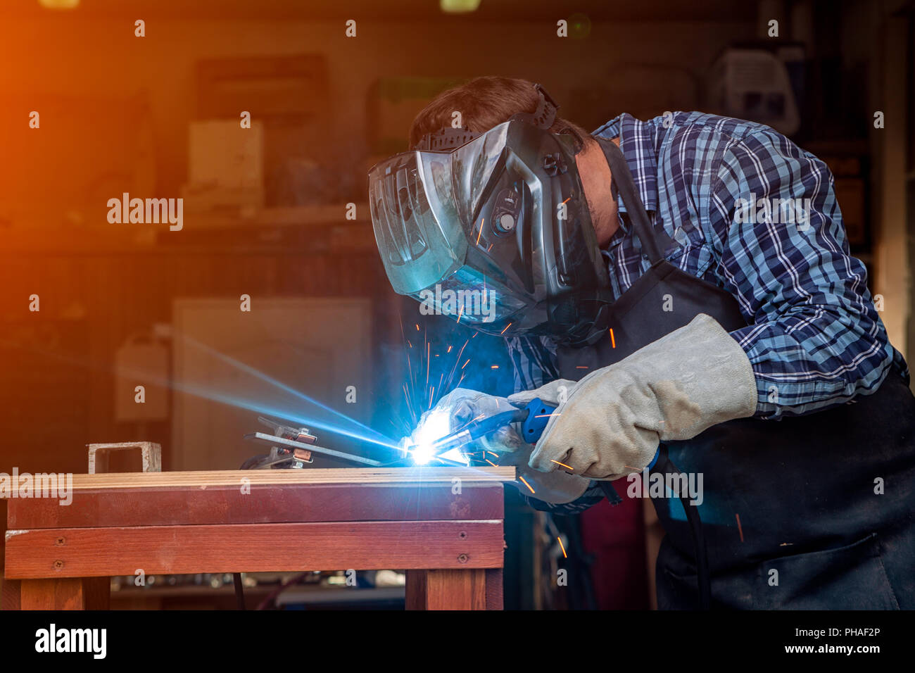 Strong Man Welder In Work Clothes Hard Working And Welds With A Welding Machine Metal In The Workshop Stock Photo Alamy