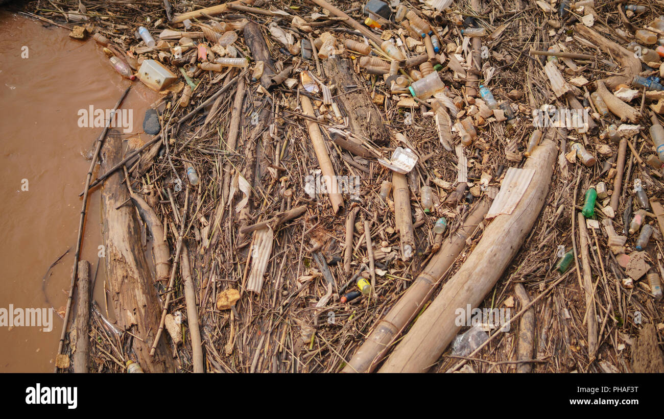 Many plastic bottles between twigs and other organic materials washed ashore on the floodplain of a wide Maekhong river,Thailand. - Stock Image