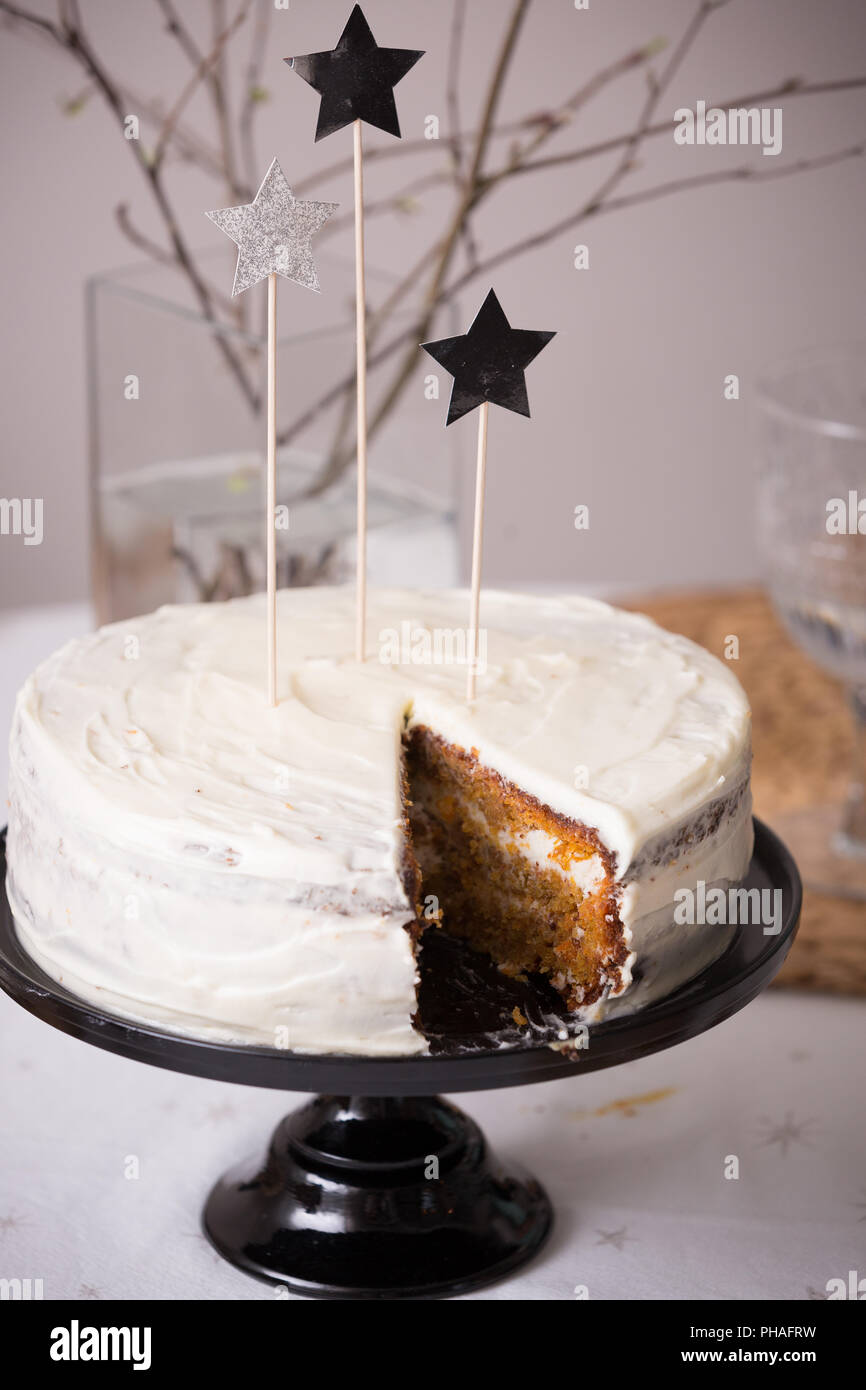 Close up of delicious homemade birthday white cake decorated with silver stars on the table. Baking at home for events. Cooking sweet cake for holiday - Stock Image