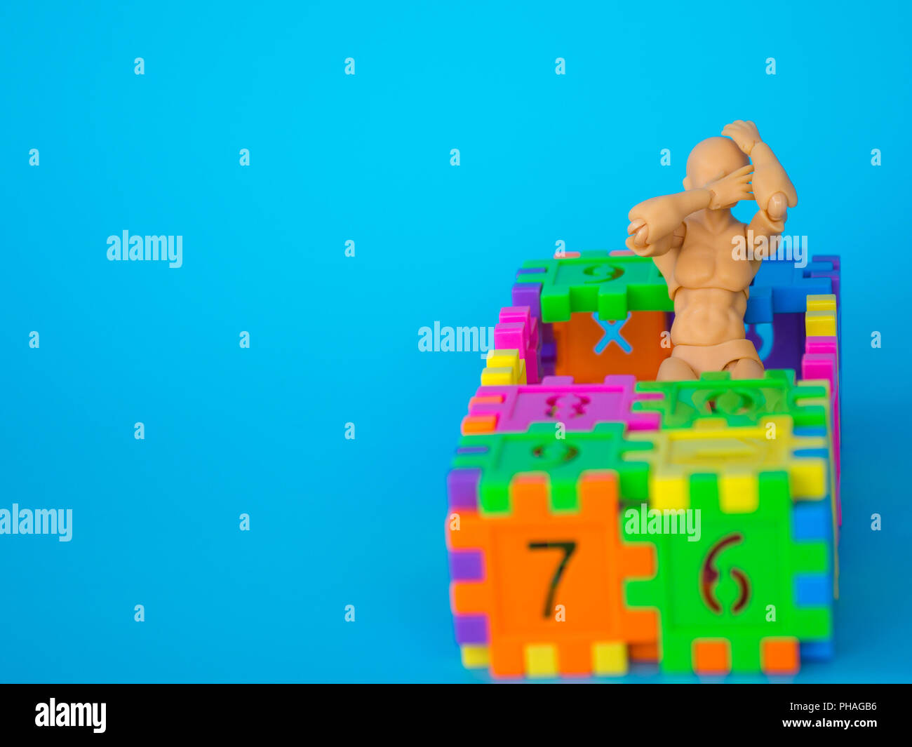 action figure standing in colorful plastic number and make a headache acting on blue background. Concept of education. copy space for text and content Stock Photo