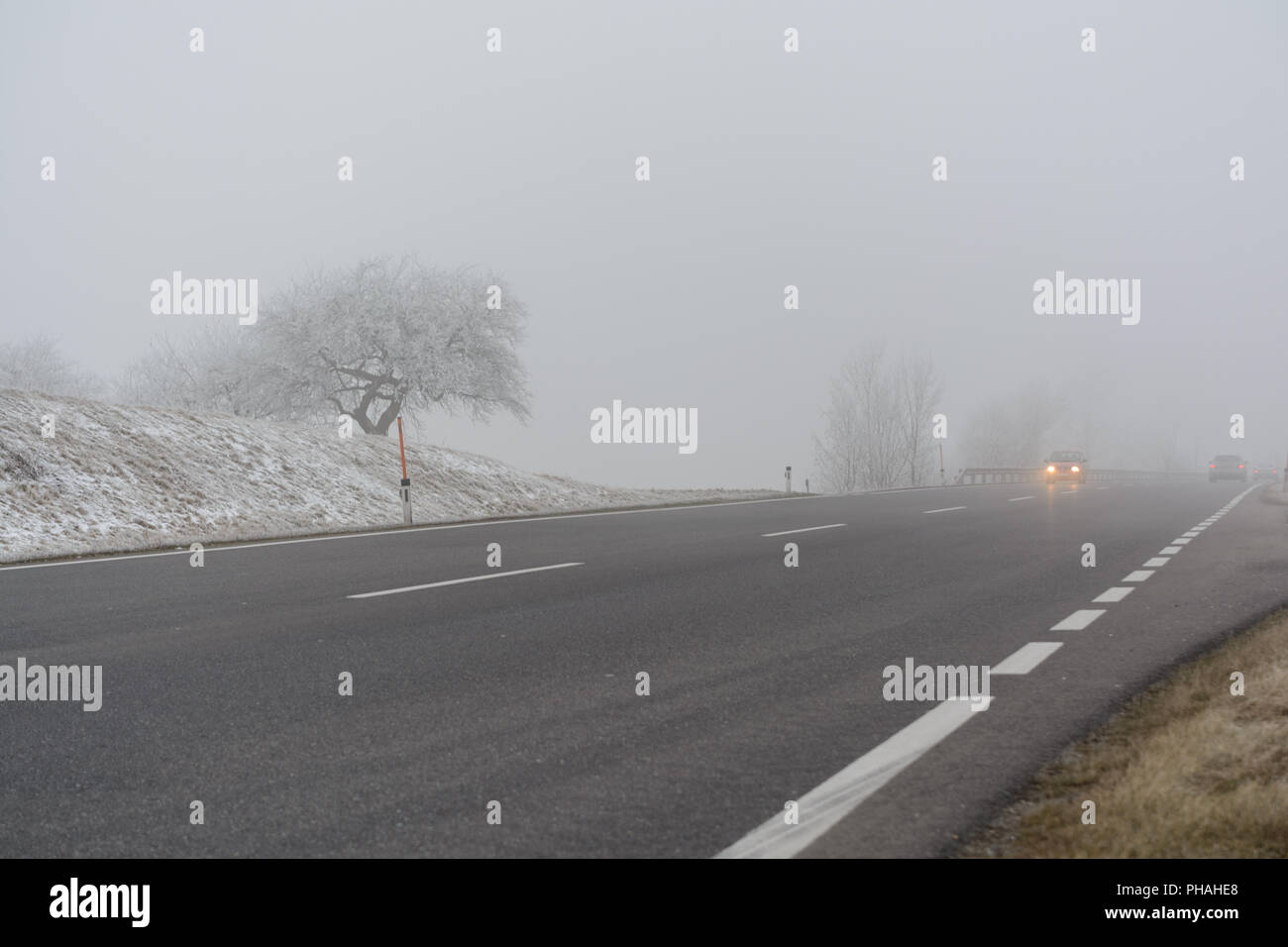 Road traffic in fog and slippery road - Stock Image
