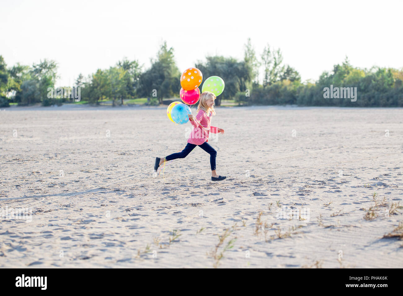 Portrait of white Caucasian teenager child girl with colorful bunch of balloons running on sand beach on sunset outdoors looking away,  happy lifestyl - Stock Image