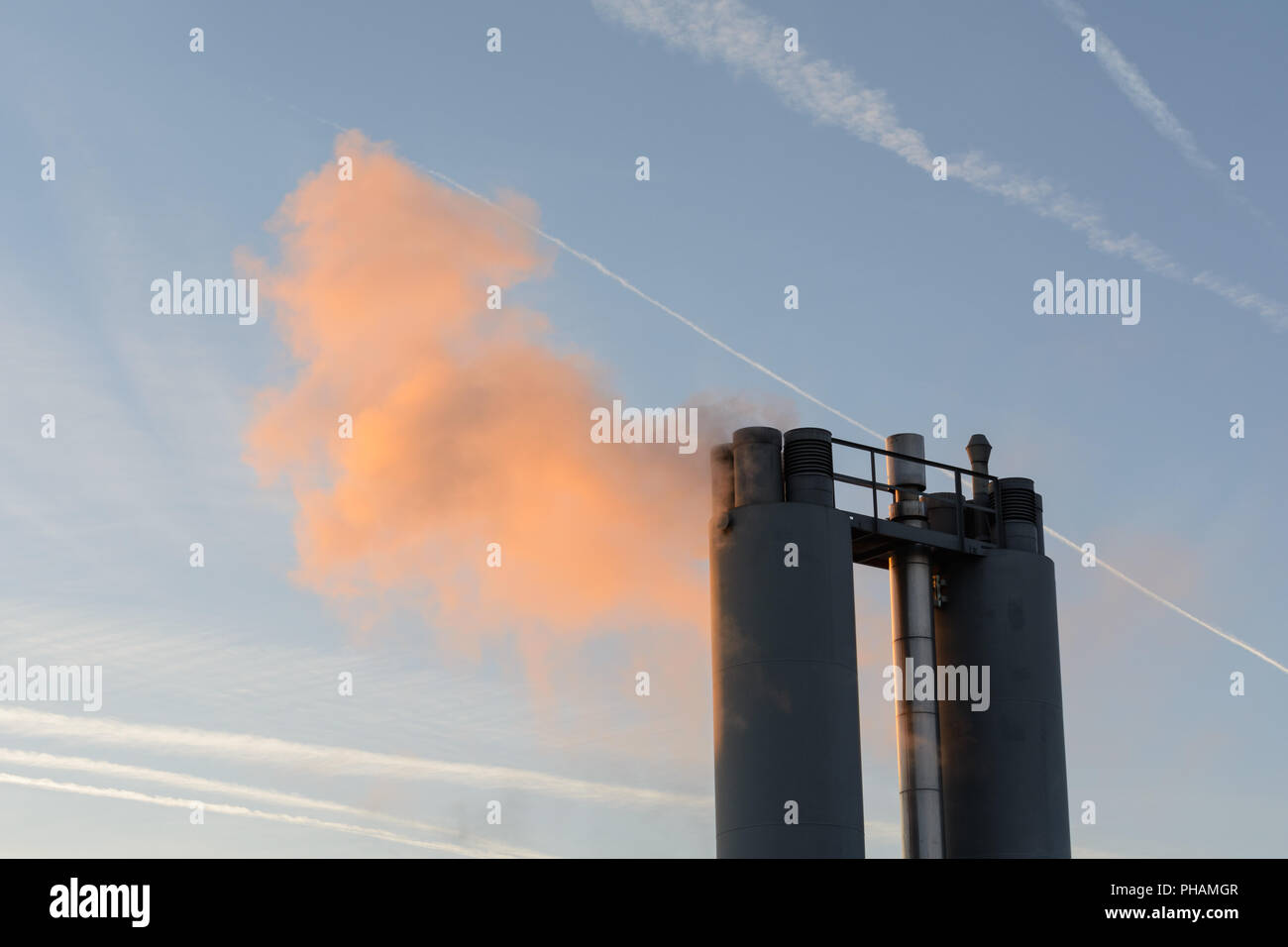 Idyllically lit smoke from industrial chimney - Stock Image