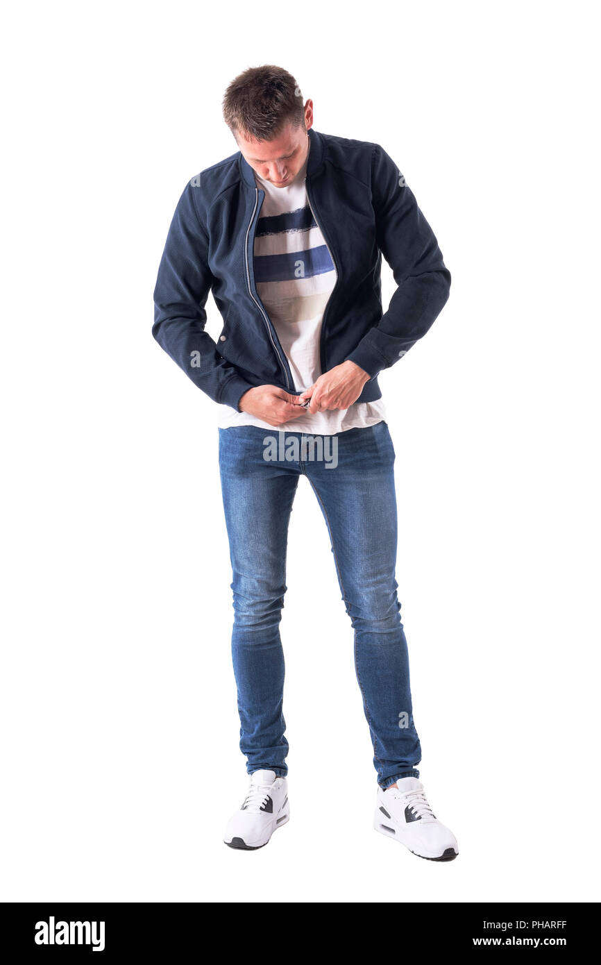 Casual young adult man get dressed zipping up bomber jacket looking down. Full body isolated on white background. - Stock Image