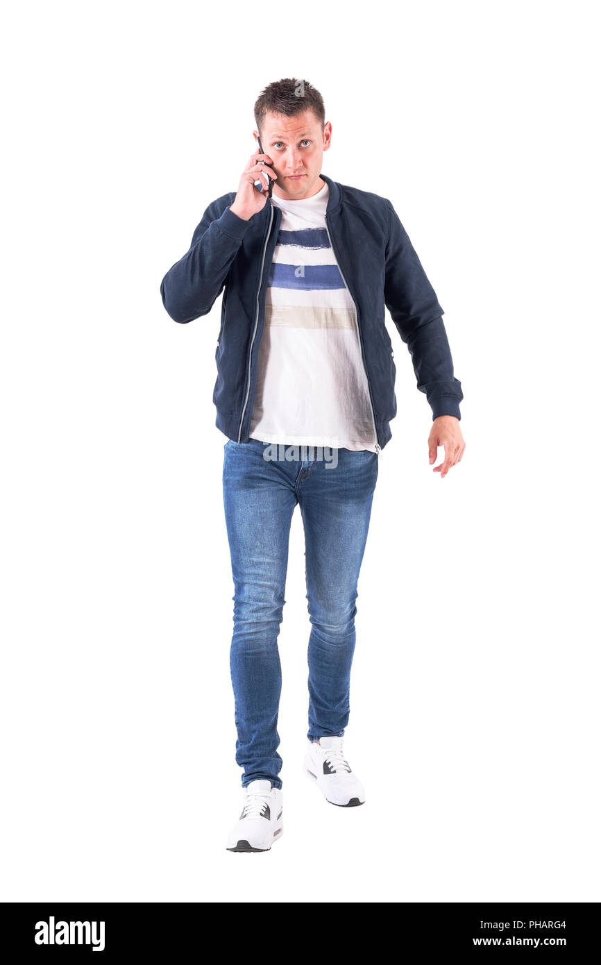 Front view of busy serious casual man talking on the phone walking with intense stare at camera. Full body isolated on white background. - Stock Image