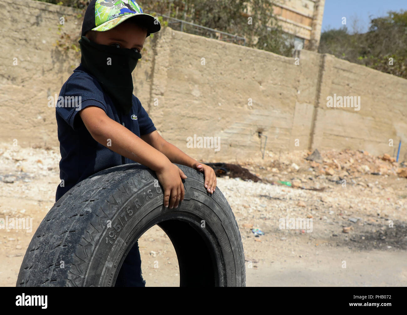 August 31, 2018 - Palestinian children and teenagers clash with the Israeli Security Forces during a weekly protest in the West Bank town of Kafr Qaddum against the confiscation of land and the closure of the town's main road. The issue of Israel constantly seizing land to build or extend Israeli settlements in the West Bank is a major stumbling block in the achievement of a peace settlement between the Palestinians and the Israelis. The residents of Kafr Qaddum have been holding weekly demonstrations since 2011 in protest against the extension of the nearby Israeli settlement of Kadumin, t - Stock Image