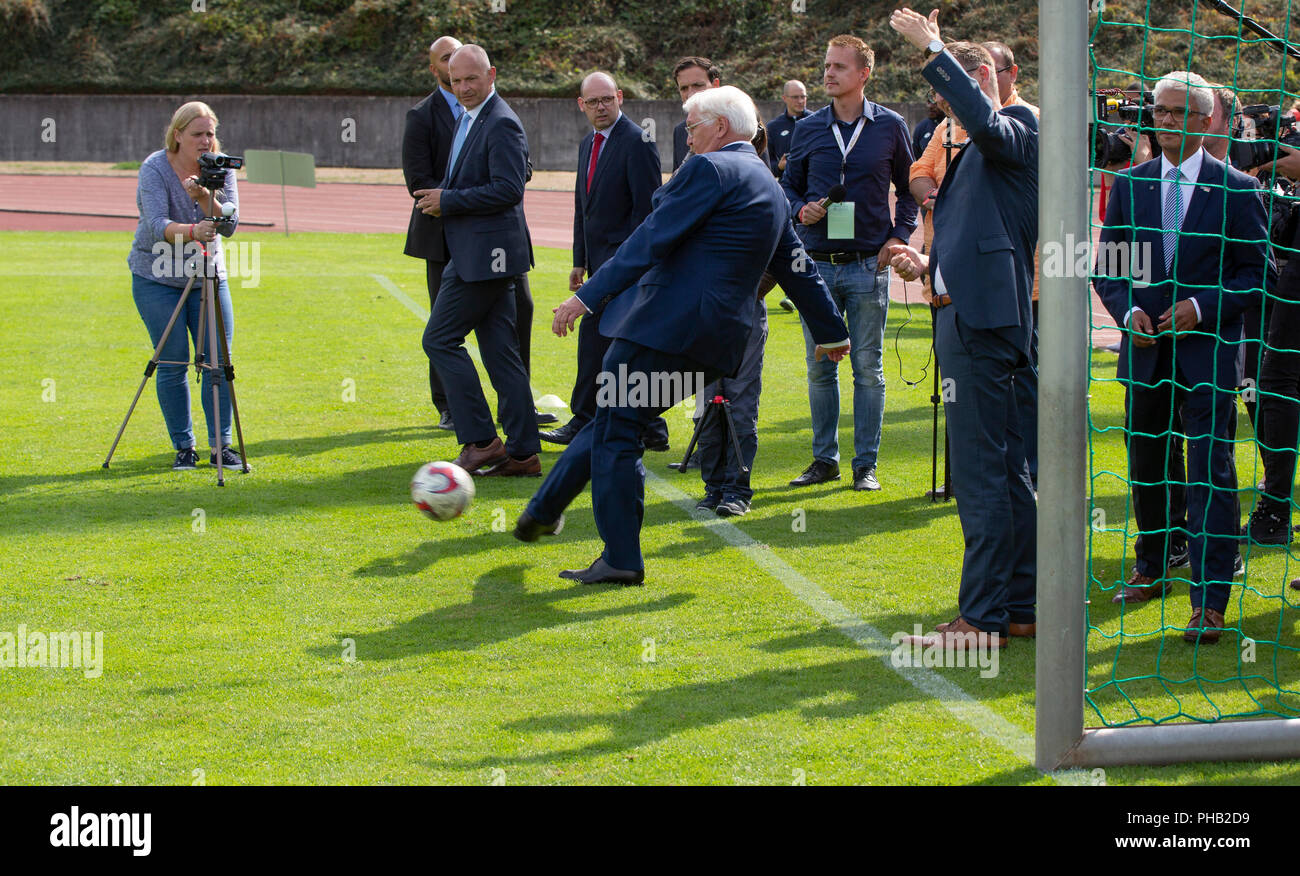 Bonn, Germany, August 31 2018:  Federal President Frank-Walter Steinmeier kicks the ball when he visits sports club Bonner SC. Steinmeier informed himself about the integration work of the club.             Credit: Juergen Schwarz/Alamy Live News - Stock Image