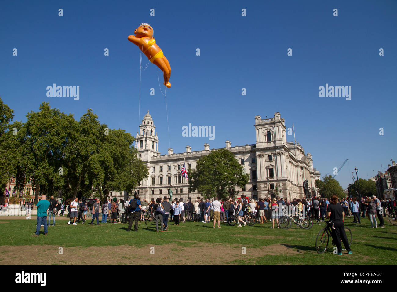 A giant balloon depicting the current London Mayor Sadiq Khan wearing a bright yellow bikini being flown over the Houses of Parliament in Westminster. - Stock Image