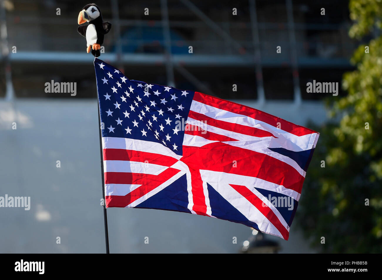London, UK.  1 September 2018.  A UK and USA flag is seen as a 29 foot giant balloon depicting Sadiq Khan, Mayor of London, wearing a yellow bikini, flies over Parliament Square.  Activist Yanny Bruere raised £58,000 to fly the balloon in protest at the Mayor's decision to allow a giant balloon of Donald Trump as a baby to be flown during his visit to the UK.  The Sadiq Khan balloon is part of Buere's 'Make London Safe Again' campaign, a reference to a surge in violent crime in London and Mr Trump's slogan 'Make America Safe Again'. Credit: Stephen Chung / Alamy Live News - Stock Image