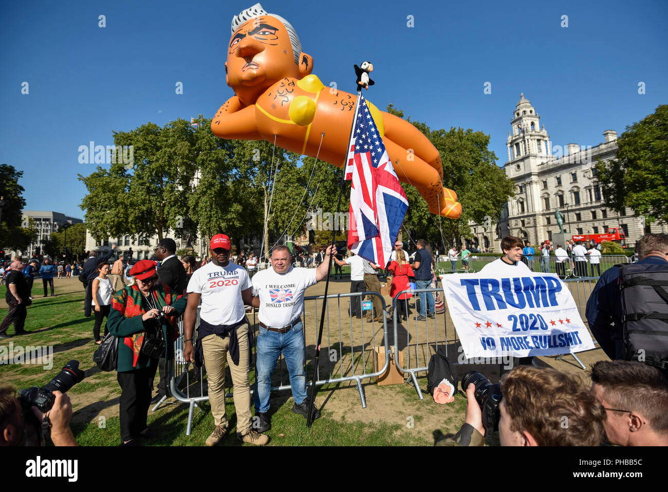 London, UK.  1 September 2018.  Donald Trump supporters stand in front of a 29 foot giant balloon depicting Sadiq Khan, Mayor of London, wearing a yellow bikini, flying over Parliament Square.  Activist Yanny Bruere raised £58,000 to fly the balloon in protest at the Mayor's decision to allow a giant balloon of Donald Trump as a baby to be flown during his visit to the UK.  The Sadiq Khan balloon is part of Buere's 'Make London Safe Again' campaign, a reference to a surge in violent crime in London and Mr Trump's slogan 'Make America Safe Again'. Credit: Stephen Chung / Alamy Live News - Stock Image