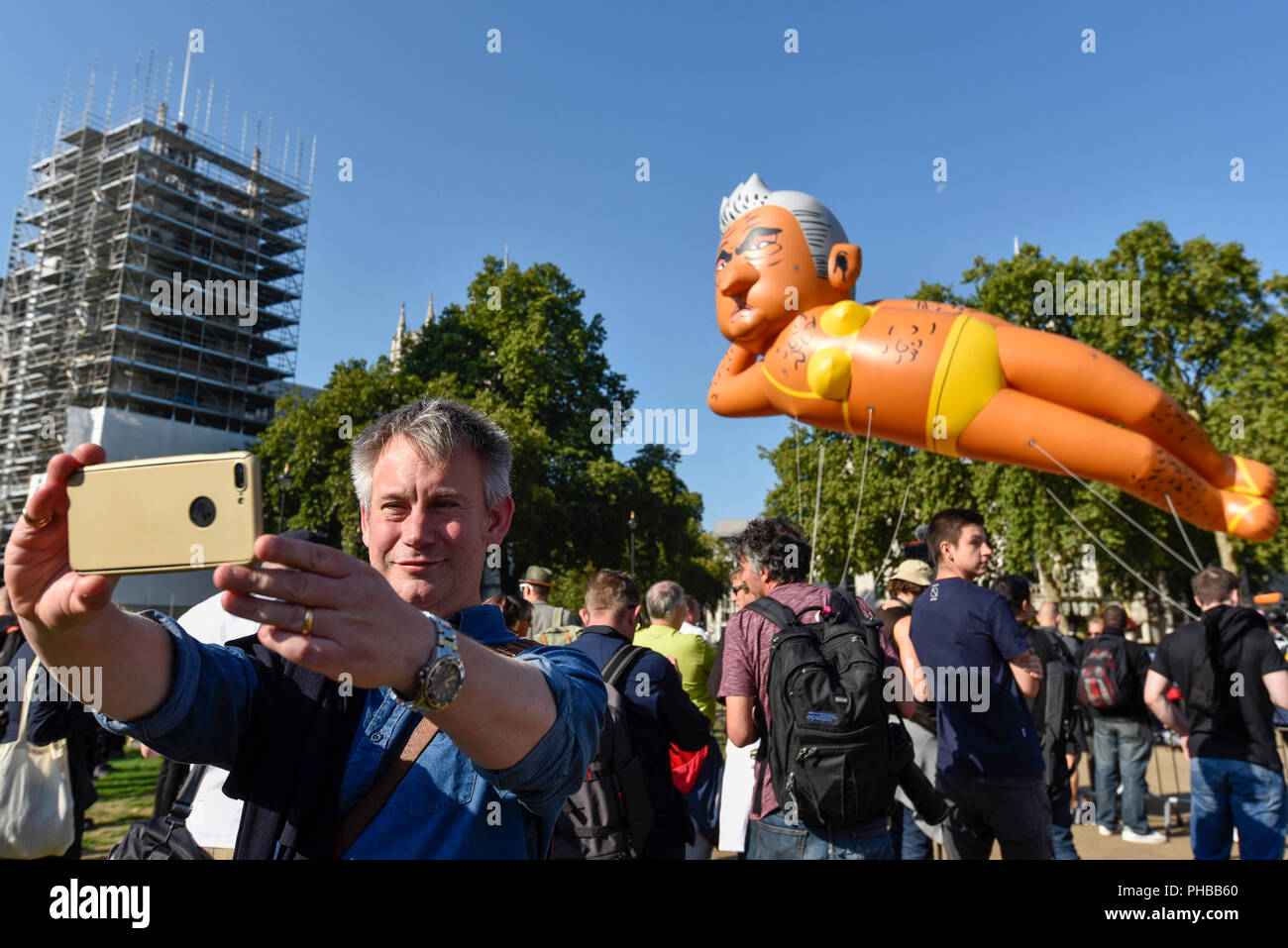 London, UK.  1 September 2018.  A man photographs a 29 foot giant balloon depicting Sadiq Khan, Mayor of London, wearing a yellow bikini, flying over Parliament Square.  Activist Yanny Bruere raised £58,000 to fly the balloon in protest at the Mayor's decision to allow a giant balloon of Donald Trump as a baby to be flown during his visit to the UK.  The Sadiq Khan balloon is part of Buere's 'Make London Safe Again' campaign, a reference to a surge in violent crime in London and Mr Trump's slogan 'Make America Safe Again'. Credit: Stephen Chung / Alamy Live News - Stock Image