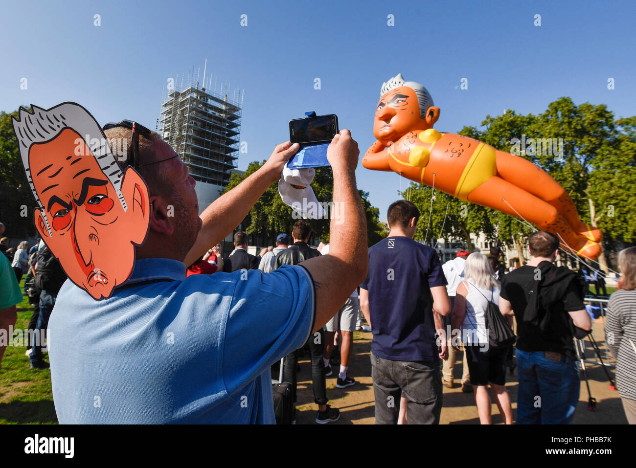 London, UK.  1 September 2018.  A 29 foot giant balloon depicting Sadiq Khan, Mayor of London, wearing a yellow bikini, flies over Parliament Square.  Activist Yanny Bruere raised £58,000 to fly the balloon in protest at the Mayor's decision to allow a giant balloon of Donald Trump as a baby to be flown during his visit to the UK.  The Sadiq Khan balloon is part of Buere's 'Make London Safe Again' campaign, a reference to a surge in violent crime in London and Mr Trump's slogan 'Make America Safe Again'. Credit: Stephen Chung / Alamy Live News - Stock Image