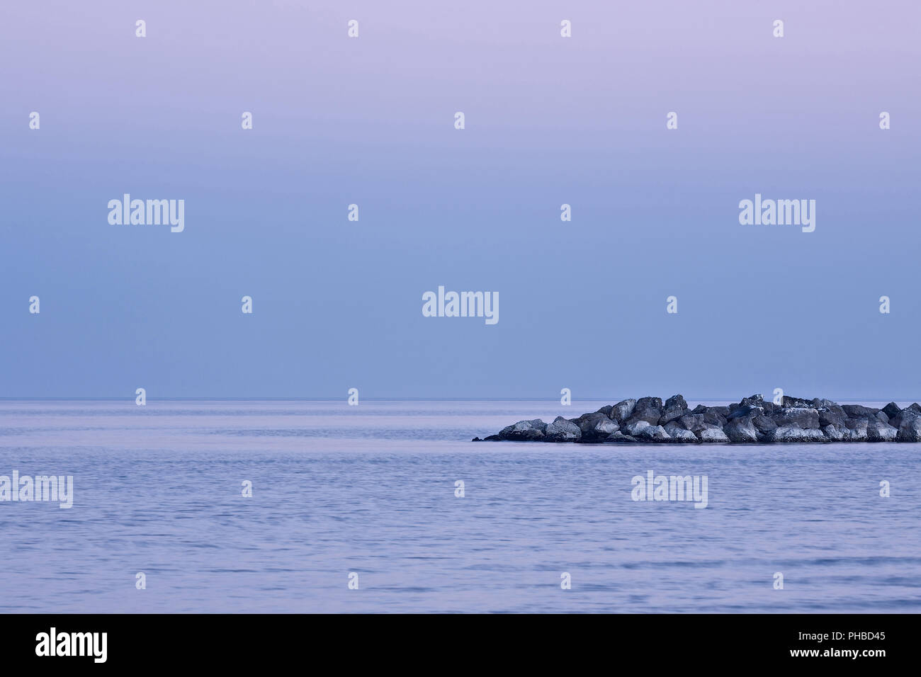 Magenta sunset over a quiet sea - Stock Image