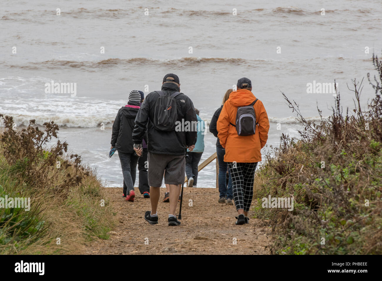 older or middle aged walkers on the isle of wight coastal path at chale on the isle of wight coastline or shoreline. - Stock Image