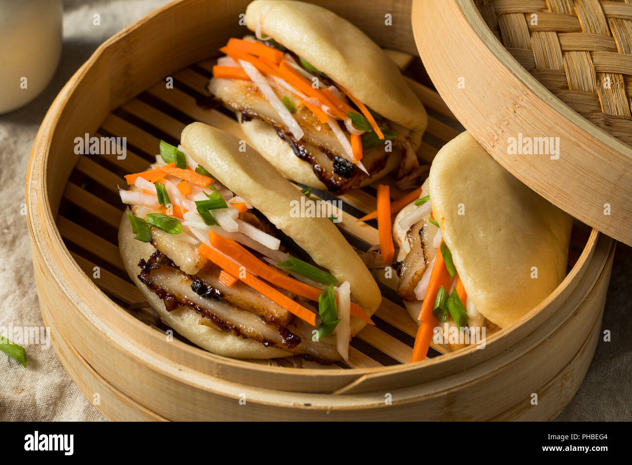 Homemade Steamed Pork Belly Bao Buns with Veggies - Stock Image