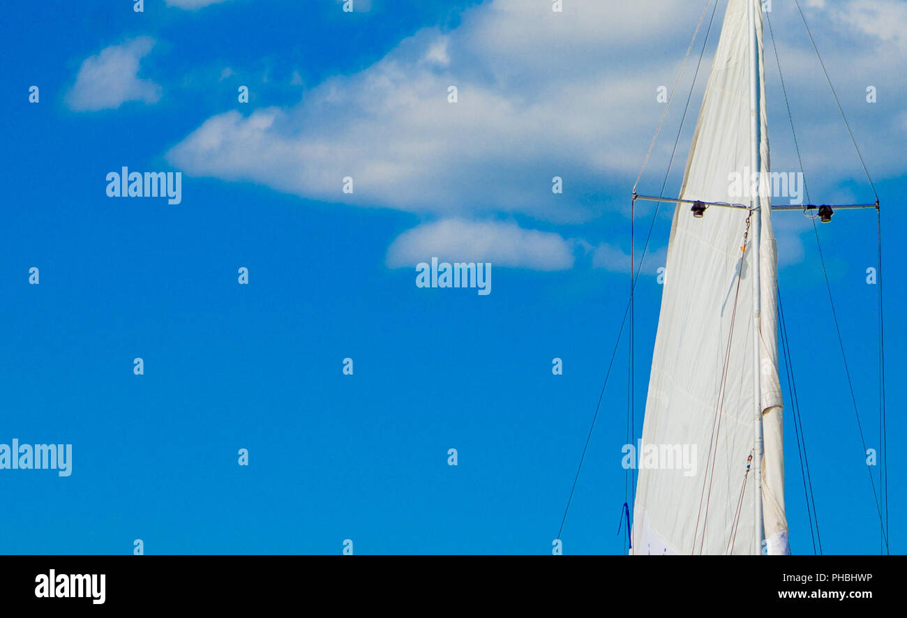 White yacht sails in sunlight on blue cloudy sky background  View
