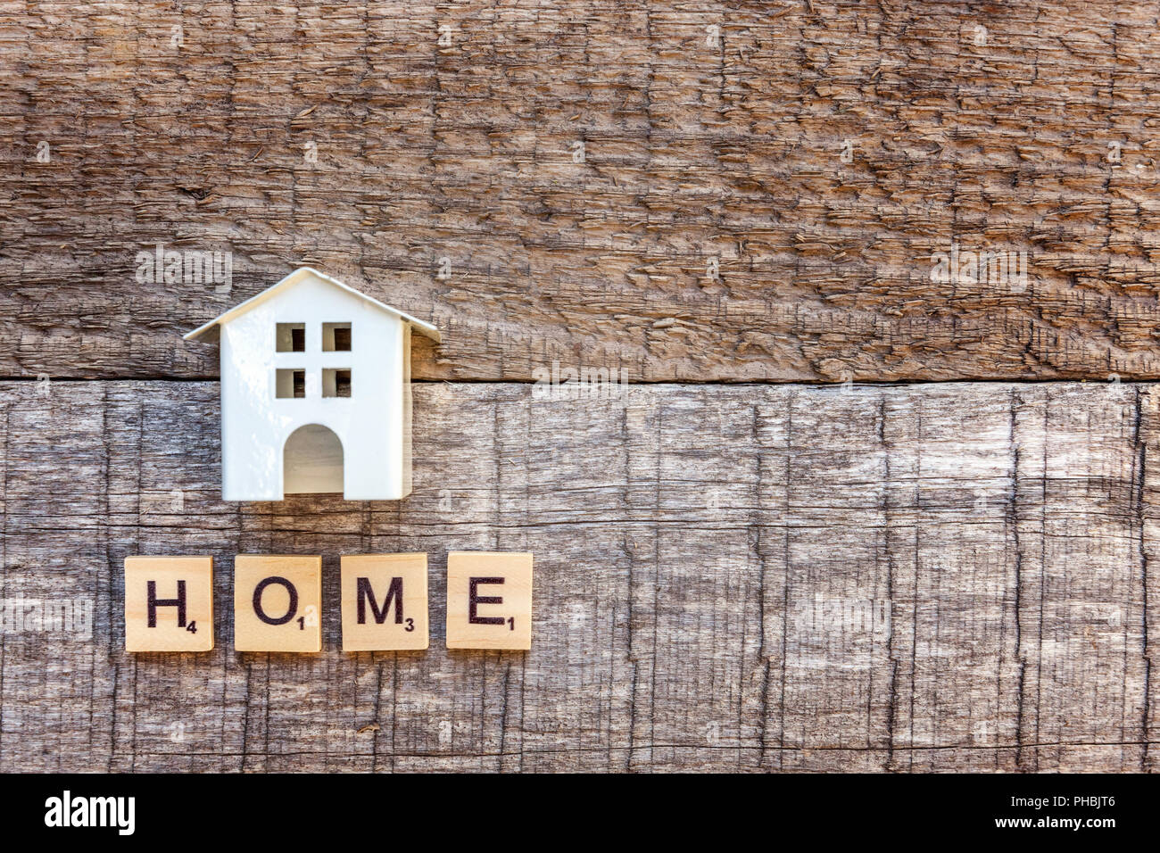 Miniature toy model house with inscription HOME letters word on wooden backdrop. Eco Village, abstract environmental background. Real estate mortgage property insurance sweet home ecology concept - Stock Image