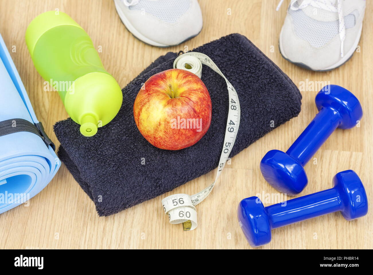 Apple with tape measure on towel with fitness equipment around - Stock Image