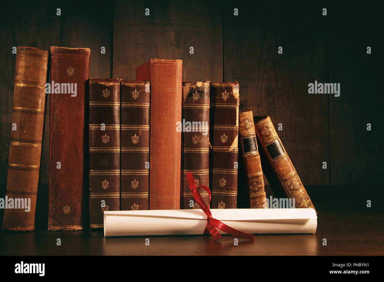 Stack of old books with diploma on desk - Stock Image