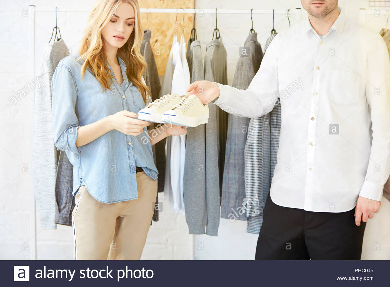 Young woman is handed shoes by shop assistant. - Stock Image