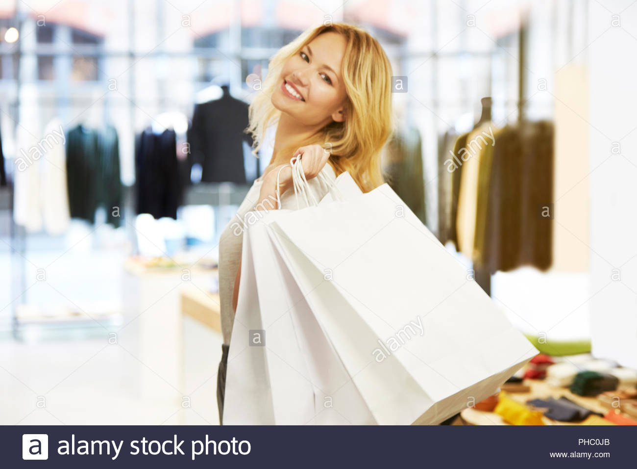 Smiling young woman holding shopping bags. - Stock Image